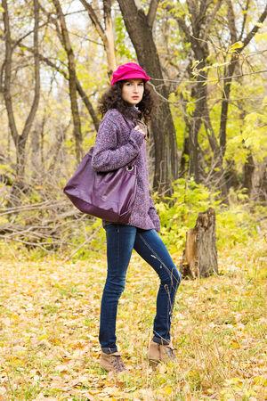 skinny jeans: Mujer con estilo joven vestido con su�ter de punto de gran tama�o, jeans ajustados, casquillo enarbolado con el bolso grande en el parque de la ciudad. Moda hermosa ni�a
