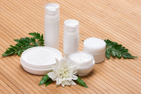 Jars of cream with white flower and fern leaves on wooden surface photo