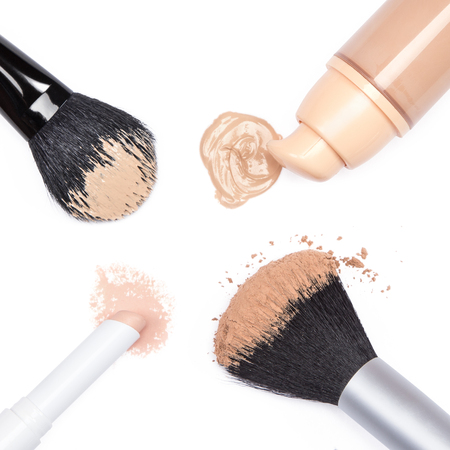 Closeup concealer pencil, foundation with open jar, loose cosmetic powder and makeup brushes on white background