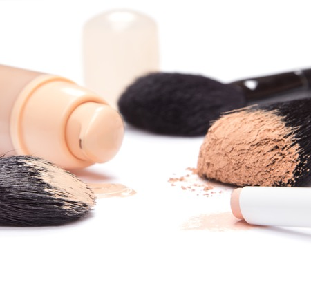 Foundation with open jar, concealer pencil and loose cosmetic powder on makeup brush on white background. Side view. Shallow depth of field