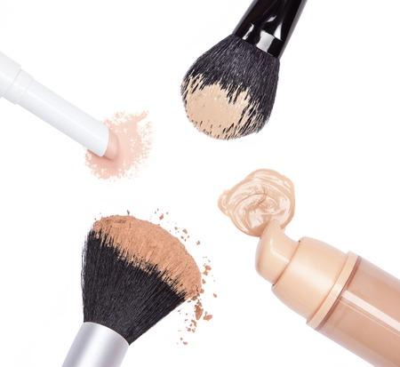 concealer: Primo piano di matita correttore, fondotinta con vaso aperto, sciolto in polvere e trucco pennelli cosmetici su sfondo bianco