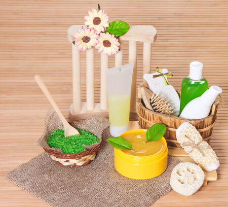 Accessories for peeling and spa: bath sea salt, shower gel, natural body scrub, shampoo, pumice, wisp, loofah with green leaves on wooden background photo