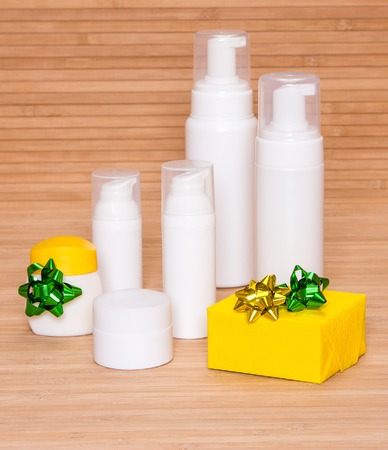 Cosmetics as a gift: different cosmetic products for body care and gift box decorated with small bows photo