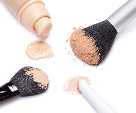 concealer: Closeup of concealer pencil, foundation with open jar, loose cosmetic powder and makeup brushes on white background Stock Photo