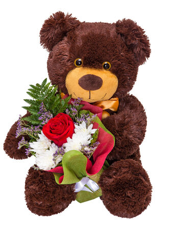 Charming smiling teddy bear holding a bouquet of fresh flowers in paws isolated on white background photo