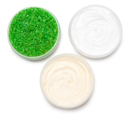 Body care cosmetic products: sea bath salt and jars filled with cream on white background, top view