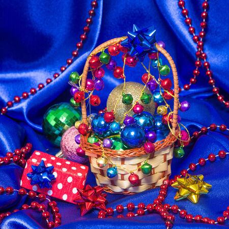 Wicker basket filled with Christmas decorations and gift box surrounded by Christmas balls and beads on blue satin fabric photo