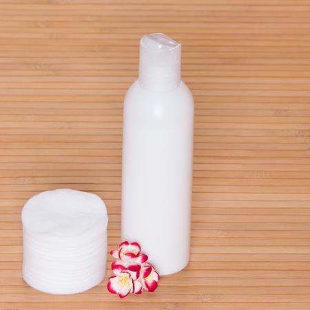 pulizia viso: Pulizia del viso e trucco rimozione prodotto cosmetico con tamponi di cotone e piccoli fiori sulla superficie in legno