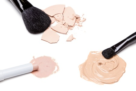 concealer: Concealer, foundation and crushed cosmetic powder with makeup brushes on white background Stock Photo
