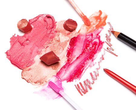 smeared: Different colors of smeared and sliced lipstick, lip gloss with brushes, lip liner on white textured surface