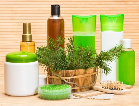 Natural hair care cosmetics and accessories: wooden basket filled with pine branches, sea salt, shampoo, conditioner, balm, mask, oil, wooden combs 스톡 콘텐츠