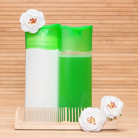 Natural shampoo and hair conditioner bottles with a wooden comb and apple blossoms on a bamboo mat Banque d'images