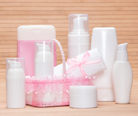 skincare products: Different skincare products with a charming wicker basket and towel on a bamboo mat. White and pink colors