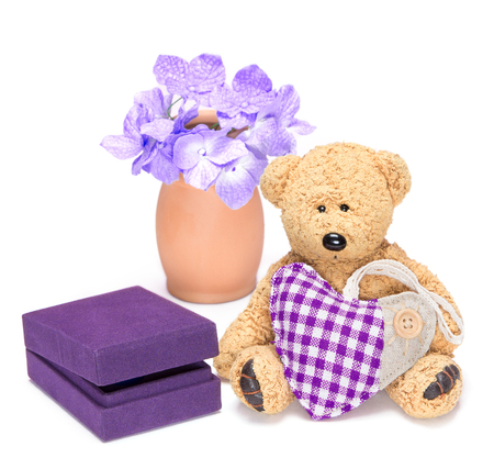 Charming teddy bear with fabric heart sitting next to gift box for jewelry on white background photo