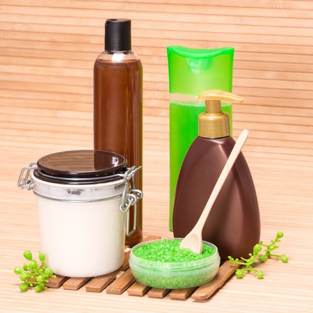 Spa and body care cosmetics: sea salt with a wooden spoon, body oil, shower gel, shampoo, liquid soap on wooden surface