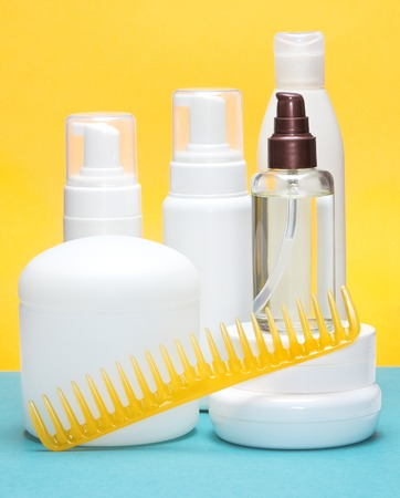 Different hair styling products with wide tooth comb on blue and yellow bright background