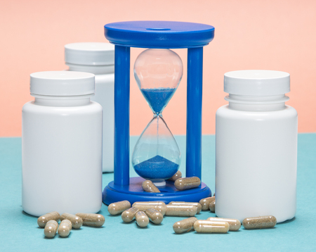 longevity drugs: Anti-aging supplements concept: scattered capsules with white plastic jars and hourglass