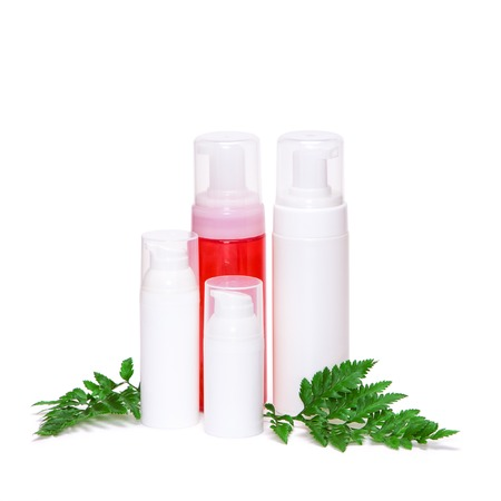 Different skincare products with green fern leaves on white background