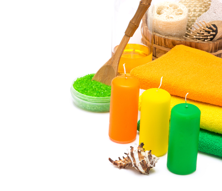 Bright bathing accessories for excellent summer mood. Candles, towels, sea salt, shower gel. Pumice, loofah, wisp, massage comb in wooden basket. Orange, green, yellow colors, white background Stock Photo