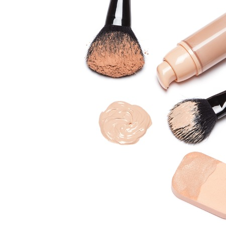 Closeup of foundation with open jar, makeup brushes and cosmetic sponge on white background. Copy space