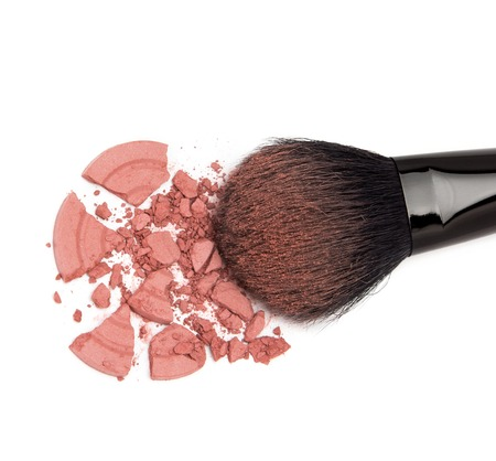 cheekbones: Closeup of crumbled powder blush pink color with makeup brush on white background
