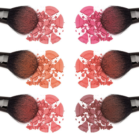 powders: Closeup of crumbled powder blush different color shades with makeup brush on white background