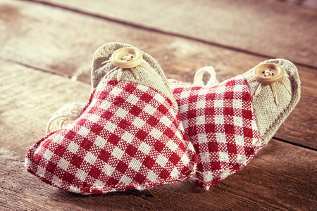 felicitation: Closeup of two rag hearts on wooden planks. Romantic concept. Toned image in retro style