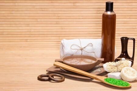 crock: Spa and pampering products and accessories: sea salt, pumice, loofah, wisp of bast, bamboo utensils with water, crock, shower gel, bath towel on wooden surface. Copy space
