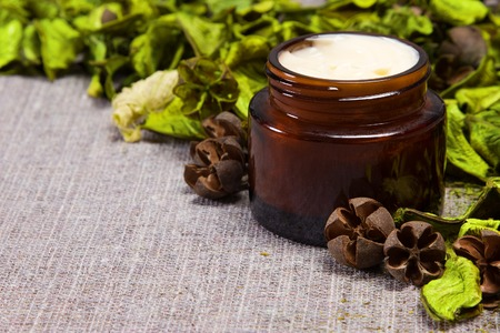 Natural skin care cream in open jar of dark glass surrounded by green leaves on sackcloth surface. Side view. Shallow depth of field. Diagonal frame. Copy space