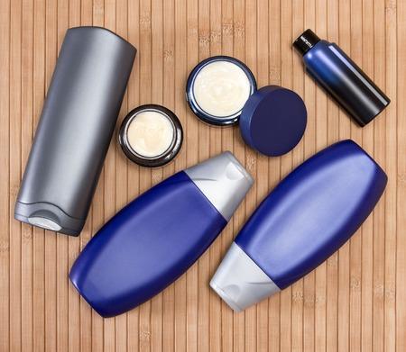productos de belleza: Cosméticos para hombre. Primer de dos frascos de vidrio abiertos llenos de crema y otros productos cosméticos para hombres en una superficie de madera. Vista superior