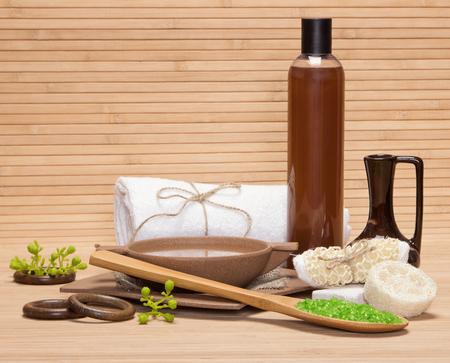 productos naturales: Spa y de cuidado del cuerpo productos y accesorios: sal marina, piedra pómez, esponja vegetal, brizna de la estopa, utensilios de bambú con agua, barro, gel de ducha, toalla de baño en superficie de madera