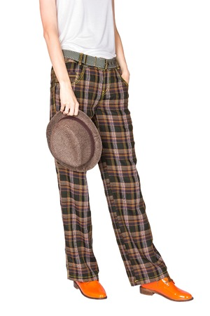 stingy: Cropped image of girl dressed in straight wide plaid pants and bright orange patent leather shoes with stingy brim hat in her hand isolated on white background