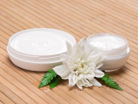 自然保湿スキンケア製品。2 つのオープン瓶のクローズ アップいっぱい濡れている白い花の横に添え、シダの葉は木の表面