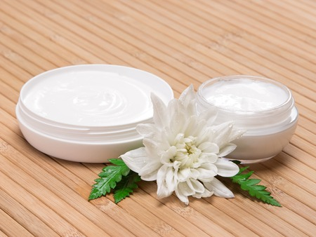 Natural moisturizing skin care products. Closeup of two open jars filled with cream next to wet white flower and fern leaves on wooden surface