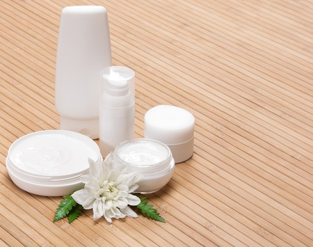 Jars of cream and other beauty products with white flower and fern leaves on wooden surface. Copy space