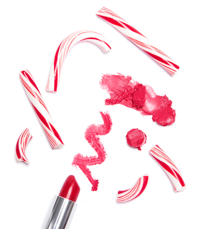 Trendy lip makeup. Bright red lipstick with crushed Christmas candy on white background