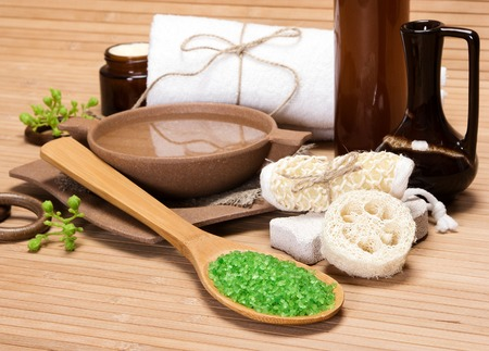Spa and pampering products and accessories: sea salt in wooden spoon, pumice, loofah, wisp of bast, bamboo utensils with water, crock, shower gel, bath towel, skin care cream