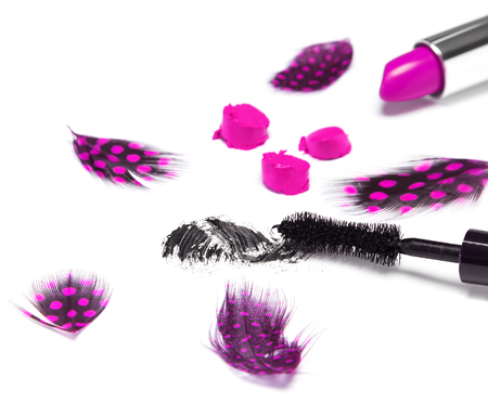 smeared mascara: Saucy makeup. Black mascara and bright purple lipstick with mottled feathers on white background. Side view. Shallow depth of field, focus on mascara brush Stock Photo