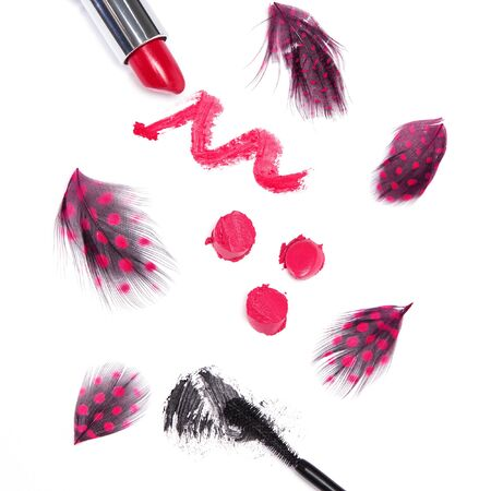smeared mascara: Saucy trendy makeup. Black mascara and bright red lipstick with mottled feathers on white background. Top view. Square crop Stock Photo