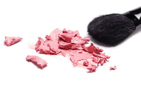 smeared: Close-up of smeared cream blush with makeup brush on white background. Shallow depth of field