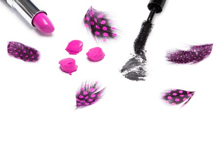 smeared mascara: Black mascara and bright purple lipstick with mottled feathers on white background Stock Photo