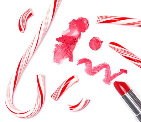 bright lipstick: Trendy lip makeup. Bright red lipstick with crushed Christmas candy on white background