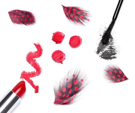 smeared mascara: Classic makeup duet concept: red lipstick and black mascara with mottled feathers on white background. Top view