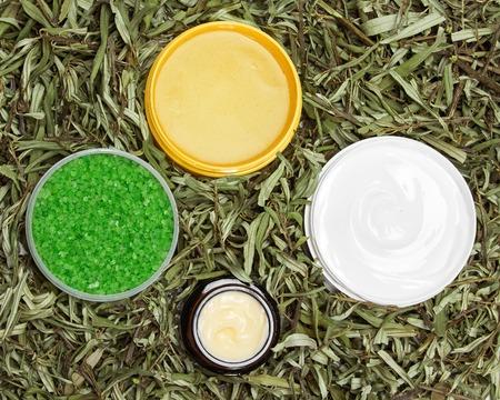productos naturales: Diferentes productos de belleza naturales en hojas verdes: exfoliante, sal marina gruesa, cremas. Cosméticos orgánicos seguras