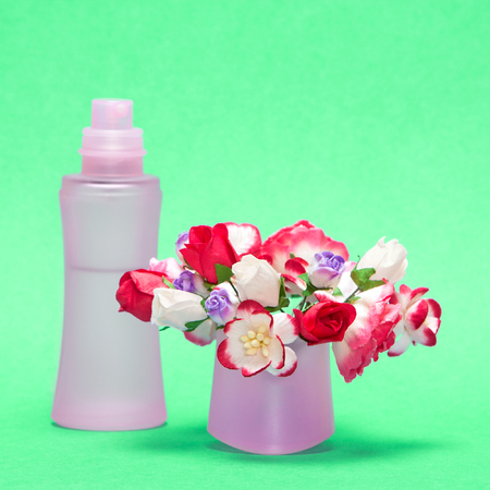 dulcet: Floral perfume. Close-up of perfume bottle behind bouquet of flowers in its cap. Focus on bouquet. Green background