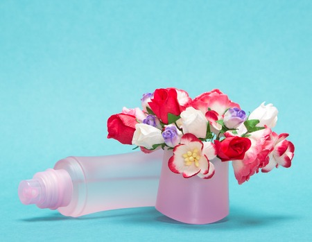 dulcet: Floral perfume. Close-up of perfume bottle lying near bouquet of flowers in its cap. Focus on bouquet. Soft blue background