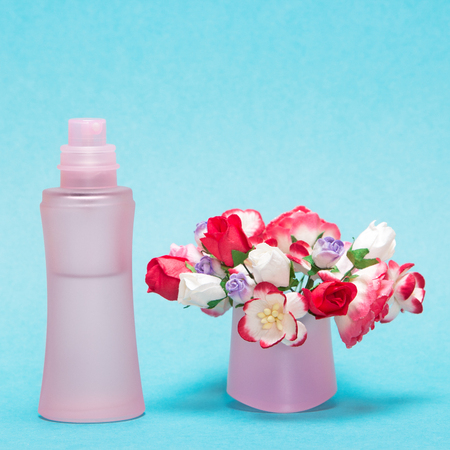 dulcet: Floral perfume. Close-up of perfume bottle with bouquet of flowers in its cap on soft blue background Stock Photo