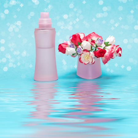 dulcet: Close-up of perfume bottle with bouquet of flowers in its cap reflected in the water surface. Cool and floral fragrance concept
