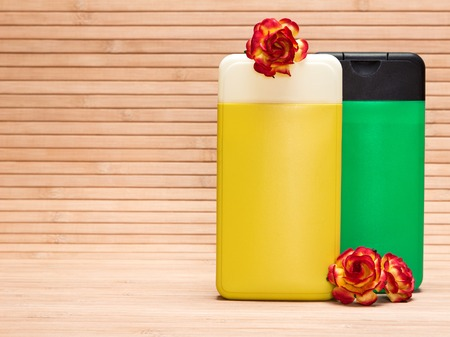 Cosmetic products for body care. Cleansing cosmetics. Closeup of bright yellow and green containers with flowers on wooden surface. Copy space