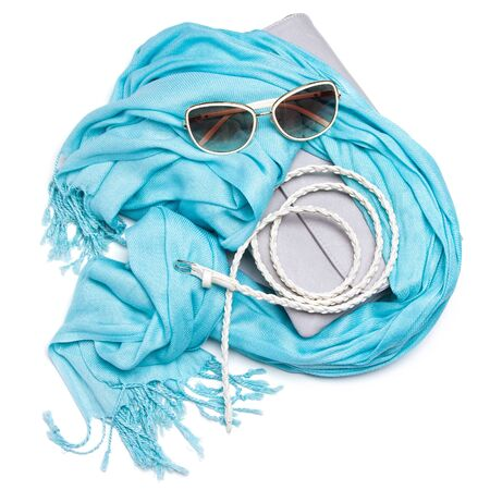 fringe: Small gray womens handbag, blue fringe scarf, skinny braided belt and sunglasses on white background